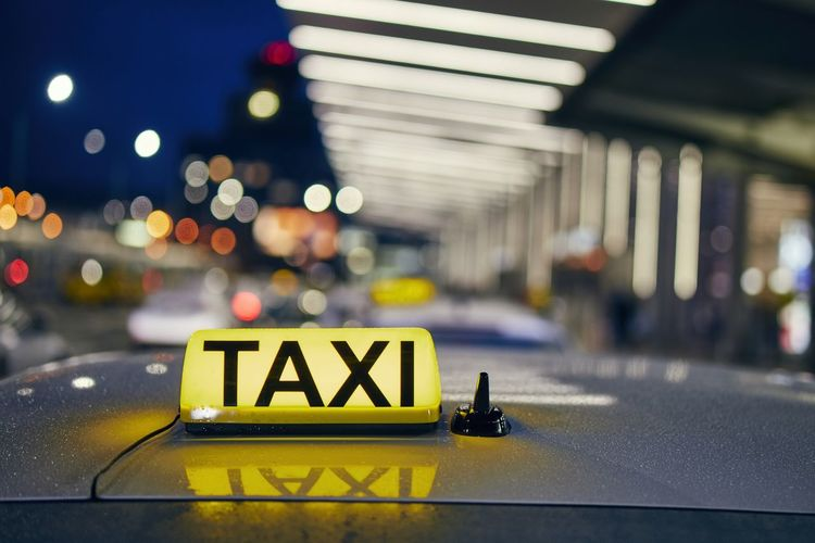 Lighting taxi sign on the roof of car against airport terminal at night. Taxi Business Car Travel Transportation Airport Airport Terminal Sign Illuminated City Street Night Yellow Text Mode Of Transportation City Life Close-up Journey Cab Reflection Urban Nightlife Traffic Driving Waiting