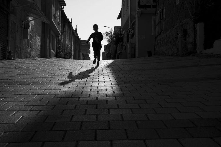 Full length rear view of man running on street
