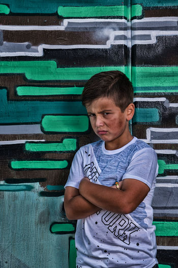 Boy with a dirty face Boy Boys Casual Clothing Child Childhood Dirty Face Front View Green Color Innocence Leisure Activity Lifestyles Looking At Camera Males  Men One Person Portrait Real People Standing Teenage Boys Teenager Three Quarter Length Waist Up
