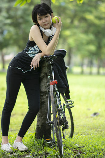 One Person Plant Real People Focus On Foreground Lifestyles Land Day Full Length Bicycle Nature Leisure Activity Grass Casual Clothing Front View Field Women Looking At Camera Green Color Outdoors Hairstyle Apples