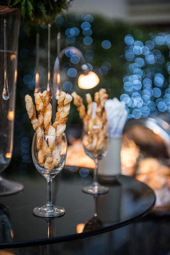 Close-up of sticks in wineglasses at table