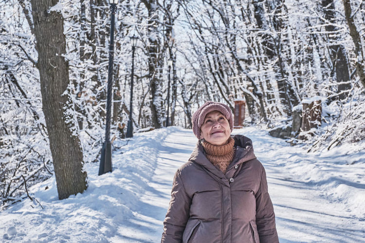 a  senior woman walking and looking up at something against the background of a winter snowy park
