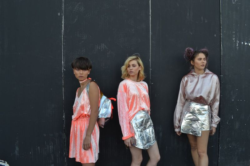 Fashionable women standing against black wall