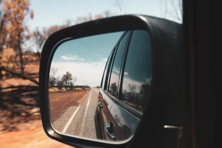 Reflection in side-view mirror of car