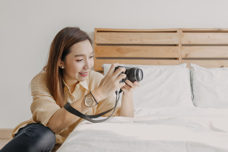 Young woman looking at camera while sitting on bed