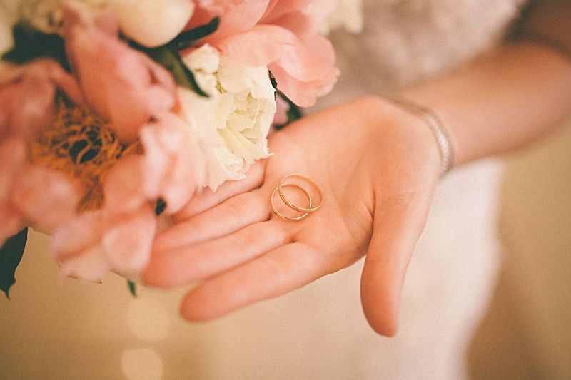 Midsection of bride holding rings
