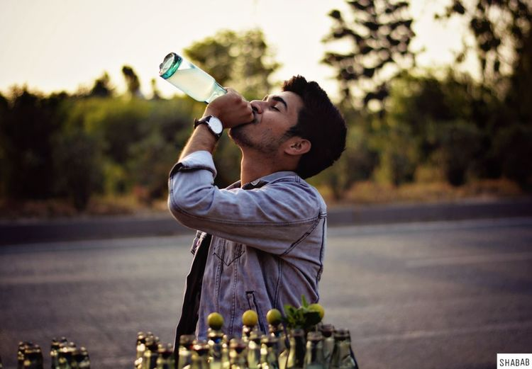 Side view of young man drinking drink from bottle on street