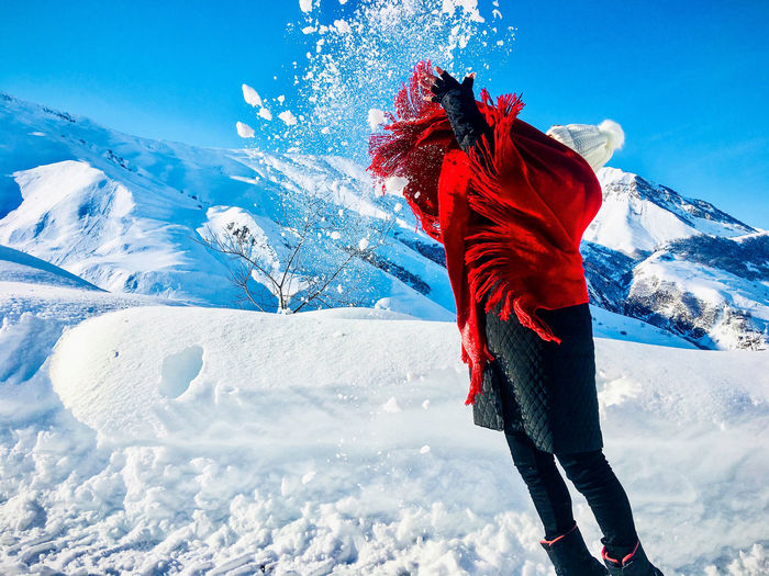 Woman playing with snow on snowcapped mountain against sky