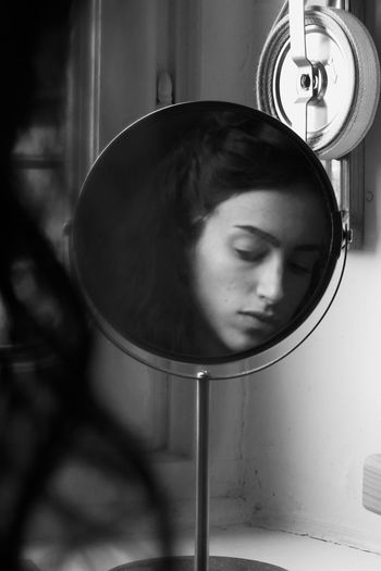 Close-up portrait of young woman looking a mirror