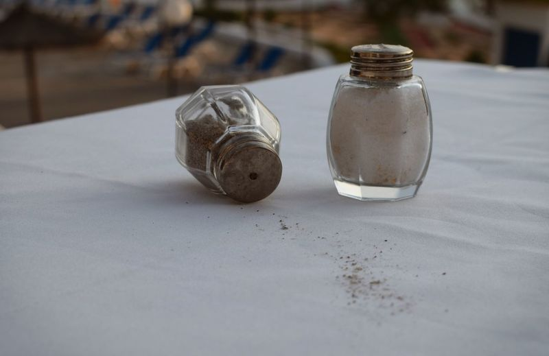 Close-up of salt and pepper shakers on table at sidewalk cafe