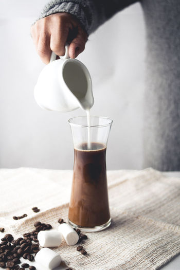 Cropped image of person pouring milk in coffee on table