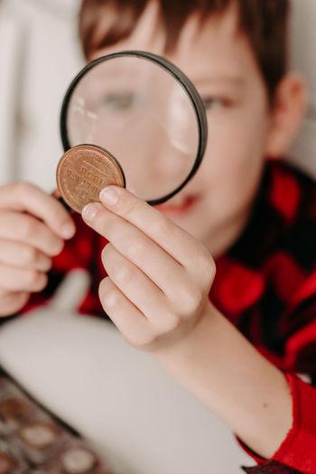 Collecting coins. the boy examines an old coin through a magnifying glass. dollars, euros
