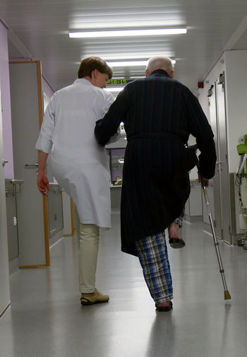 Nurse Helping Old Man Geriatrics Walking Exercices Hospital Corridor Rear View Belgium