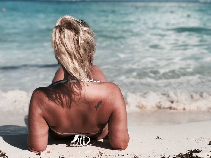 Rear view of woman relaxing on shore against sea at beach