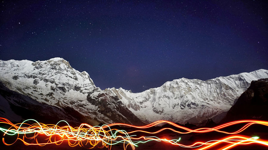 Light trails on snowcapped mountain against sky at night