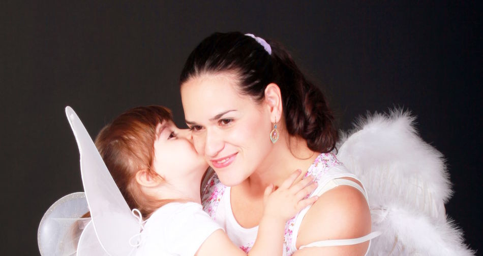 Close-up of cute girl in fairy costume kissing mother on cheek against black background