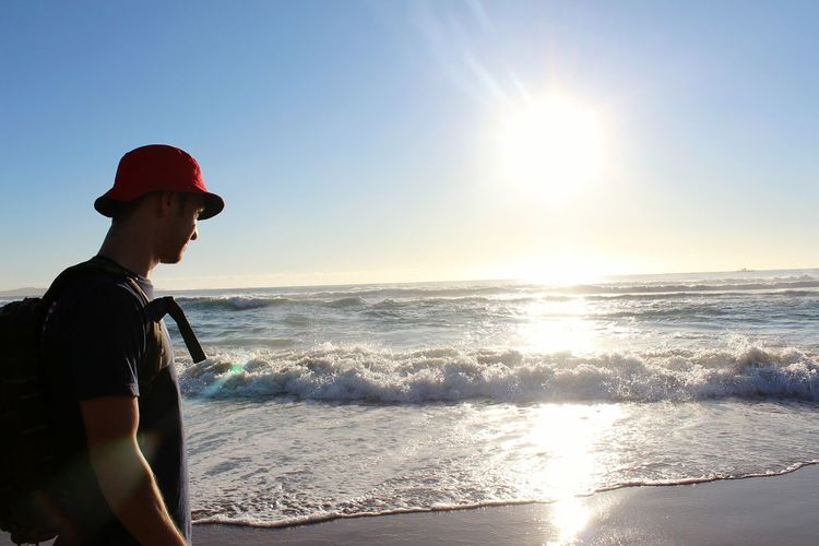 Young man standing at sea shore against bright sky