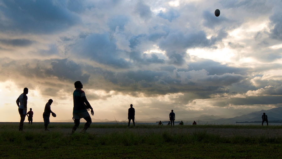 Silhouette Friends Playing Rugby On Field Against Cloudy Sky During Sunset