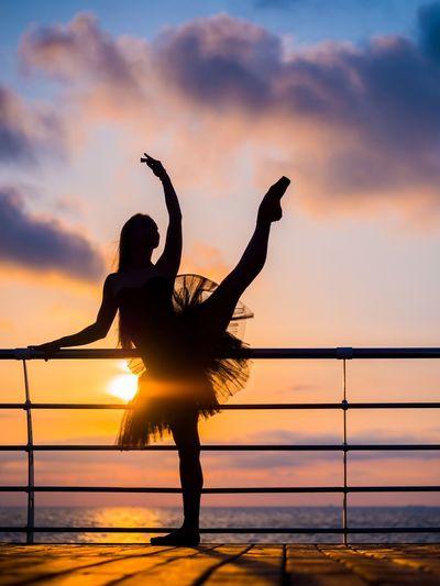 Silhouette ballet dancer dancing against sea during sunset