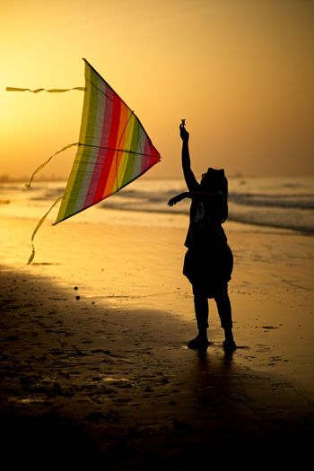 Silhouette girl holding kite while standing at beach against sky during sunset