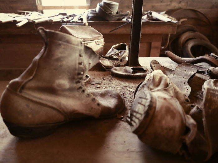 Close-Up Of Abandoned Leather Shoes In Workshop