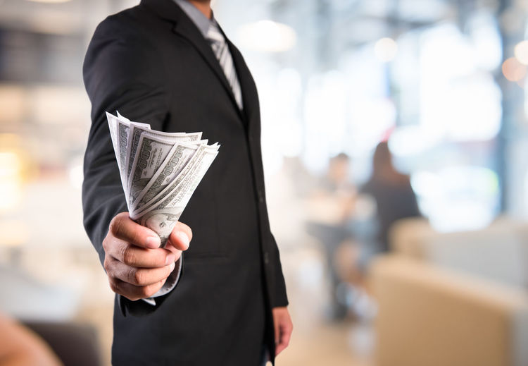 Midsection of businessman holding paper currencies at office