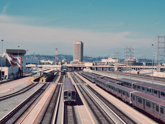 Trains on railroad track with city in background