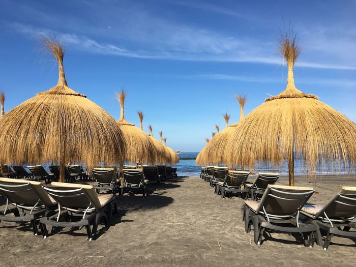 EyeEm Selects Tenerife Canary Islands Beach Sand Chair Absence Day Thatched Roof Outdoors No People Arrangement Sky Table Tranquil Scene Sea Beauty In Nature Tranquility Nature Horizon Over Water