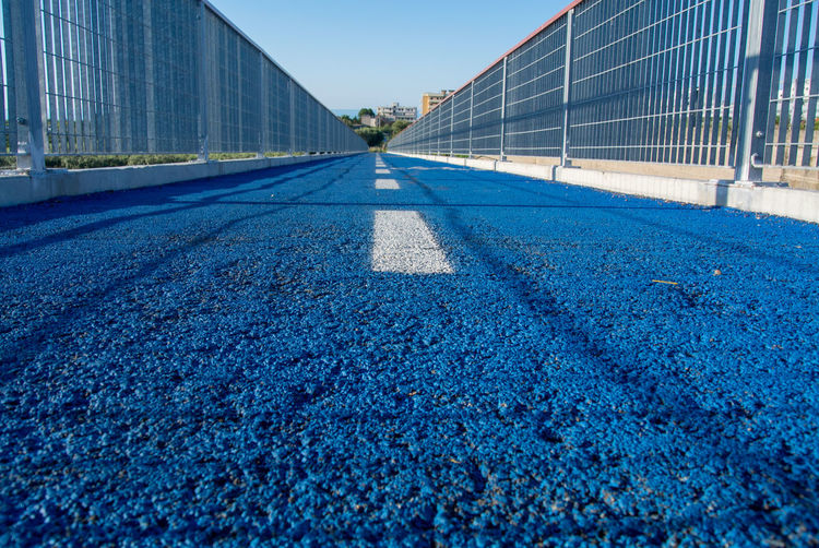Surface level of road against blue sky in city