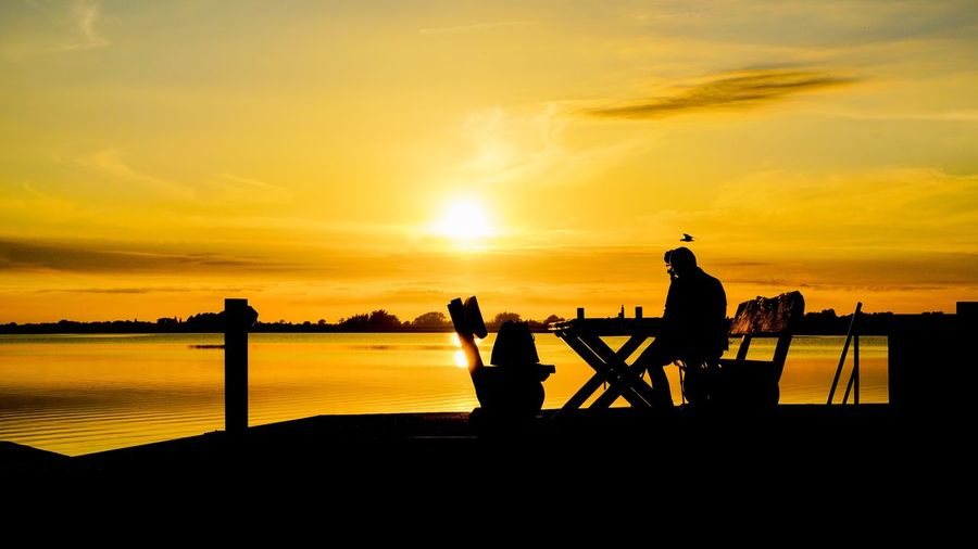 Silhouette Sunset Sky Water Sea Occupation Orange Color Cloud - Sky Beauty In Nature Nature Scenics - Nature People Standing Real People Leisure Activity Lifestyles Outdoors
