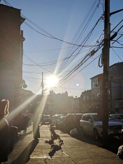 Cars on street in city against bright sun