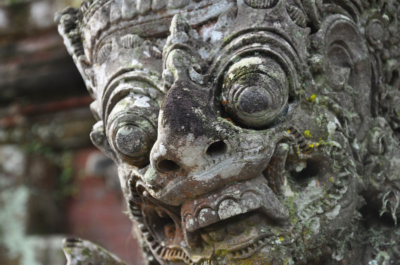 Close-up of weathered guardian statue at temple