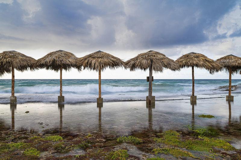 Panoramic view of rustic umbrellas on beach against sky