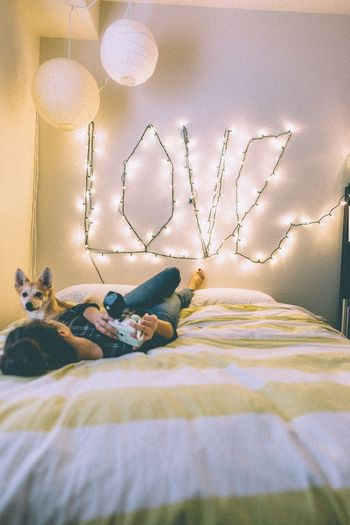 Woman With Dog Lying On Bed At Home