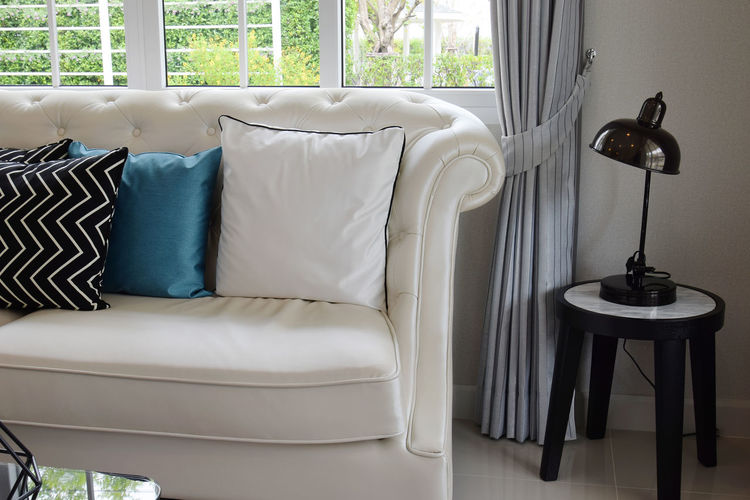white and blue pillows on a white leather couch in vintage living room Absence Armchair Chair Coffee Table Comfortable Cushion Day Domestic Room Electric Lamp Empty Furniture Home Interior Home Showcase Interior Indoors  Living Room Luxury No People Pillow Seat Sofa Stuffed Table Window