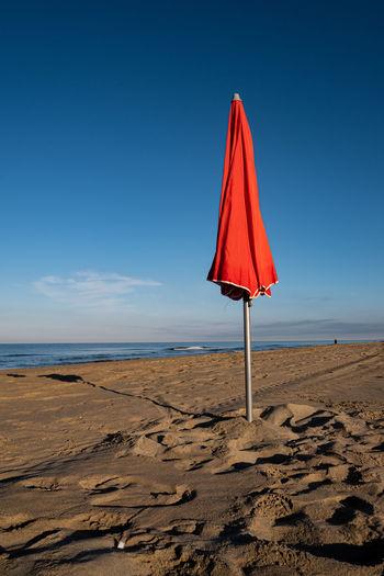 Lifeguard hut on beach against blue sky
