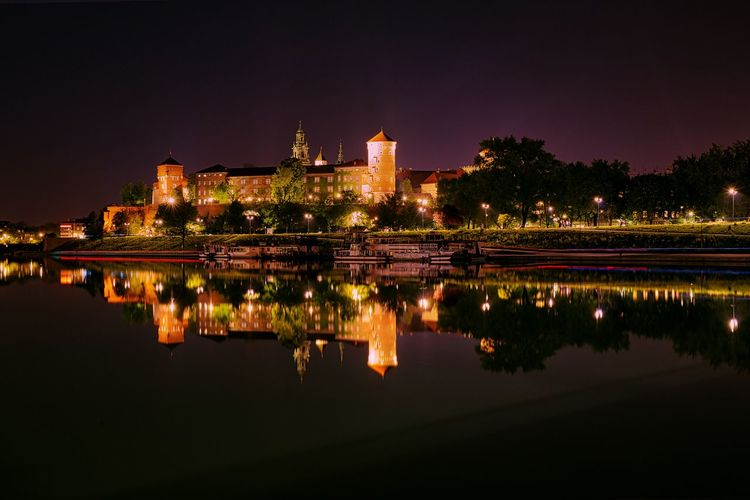 Reflection of illuminated buildings in lake against sky at night