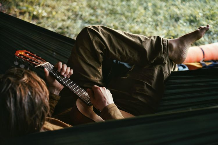 Man Playing Guitar While Sitting In Hammock
