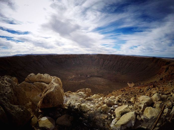 Scenic view of meteor crater against cloudy sky