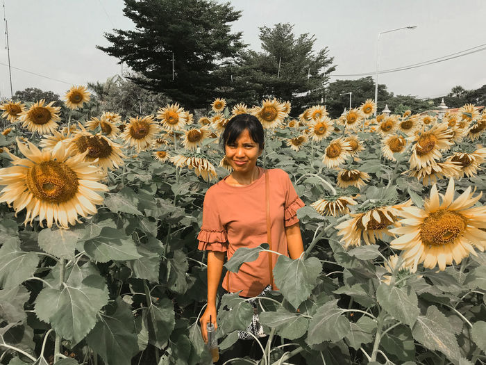 Portrait of woman standing on sunflower field