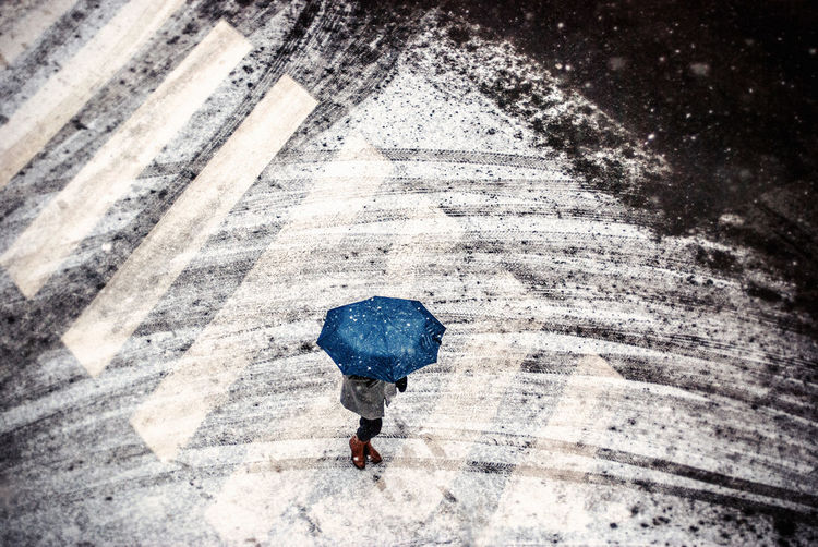 Person under blue umbrella crossing street in winter