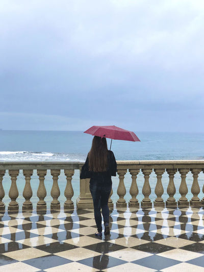 Rear view of woman standing on railing against sea during rainy season