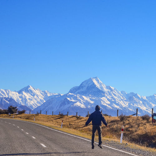 Man jumping on road with snow covered mountain in back ground. Mount Cook National Park, New Zealand Action Beauty In Nature Blue Clear Sky Cold Temperature Copy Space Daring Day High Achiever Landscape Leisure Activity Men Mountain Mountain Range Nature One Person Outdoors People Real People Rear View Road Scenics Sky Snow Winter