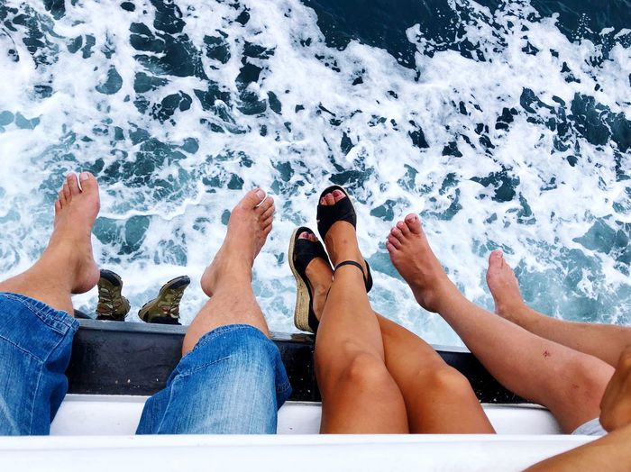 Low section of people sitting on boat at sea