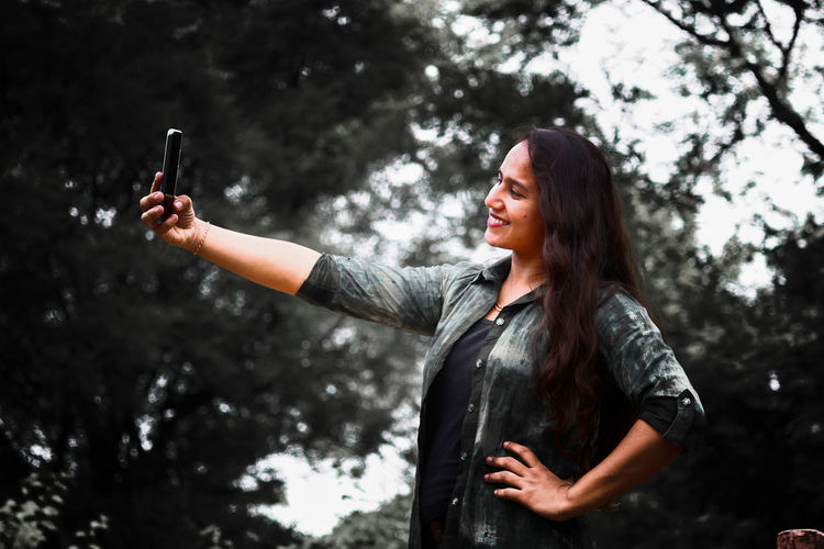 Smiling young woman taking selfie with phone while standing against tree