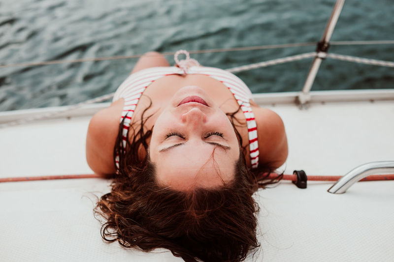 Directly above shot of woman sleeping in boat on sea