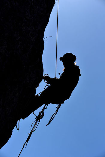 Silhouette of a rock climber hanging on the wall in the way to the summit Adrenaline Adventure Cliff Climber Climbing Climbing A Mountain Endurance Extreme Extreme Sports Hang Hanging Height Helmet Mountain Mountaineer RISK Rock Rock Climber Rope Silhouette Sky Sport Summit Sun Sunset