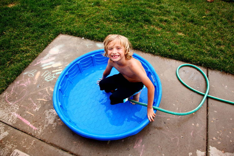 Portrait Of Smiling Shirtless Boy In Wading Pool In Back Yard
