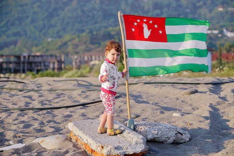 a girl and abkhazian flag Abkhazia Abkhazian Flag Child Childhood Full Length Standing Girls Flag Patriotism Blond Hair Sky Babyhood Sand Shore Beach Sandy Beach Summer Road Tripping My Best Travel Photo A New Beginning Moms & Dads