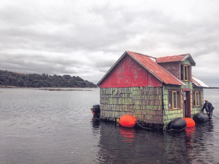 Minga: Tradición de Chiloé, donde se traslada una casa de un lugar a otro. Water Sky Cloud - Sky Waterfront Architecture Built Structure Building Exterior Outdoors Nature Real People Beauty In Nature Mountain Day House Moving Home Minga Sea Life Wood Wood - Material Island Island Life Floating On Water Floating Rural